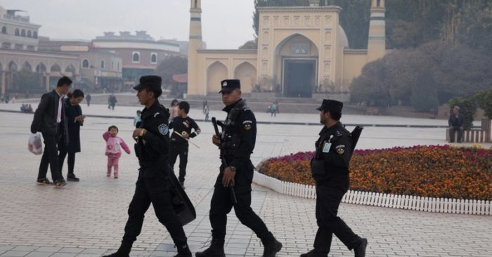 """FILE - In this Nov. 4, 2017 file photo, Uighur security personnel patrol near the Id Kah Mosque in Kashgar in western China's Xinjiang region. China's northwestern region of Xinjiang has revised legislation to allow the detention of suspected extremists in """"education and training centers."""" The revisions come amid rising international concern over a harsh crackdown in Xinjiang that has led to as many as 1 million of China's Uighurs and other Muslim minorities being held in internment camps. (AP Photo/Ng Han Guan, File)"""