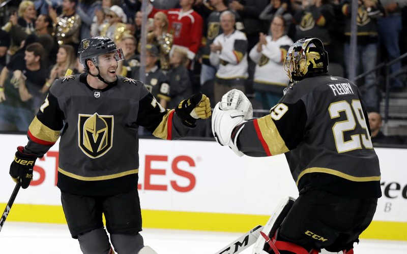 Vegas Golden Knights goalie Marc-Andre Fleury (29) congratulates defenseman Brad Hunt (77) after he scored against the Carolina Hurricanes during the first period of an NHL hockey game Saturday, Nov. 3, 2018, in Las Vegas. (AP Photo/Isaac Brekken)