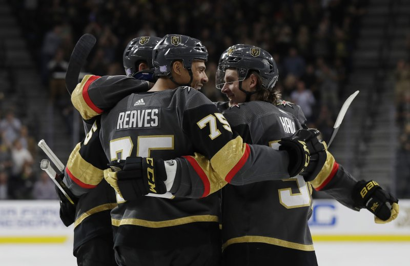 Vegas Golden Knights right wing Ryan Reaves (75) is congratulated on his goal by teammates, including Erik Haula (56), who had an assist, during the second period against the Carolina Hurricanes in an NHL hockey game Saturday, Nov. 3, 2018, in Las Vegas. (AP Photo/Isaac Brekken)