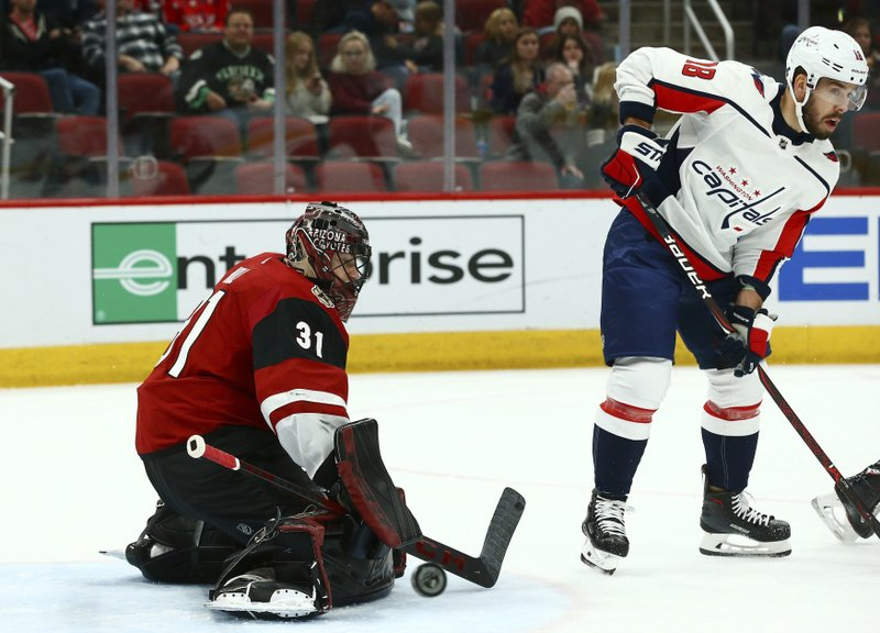 Arizona Coyotes goaltender Adin Hill (31) makes a save on a deflection from Washington Capitals center Chandler Stephenson (18) during the first period of an NHL hockey game Thursday, Dec. 6, 2018, in Glendale, Ariz. (AP Photo/Ross D. Franklin)