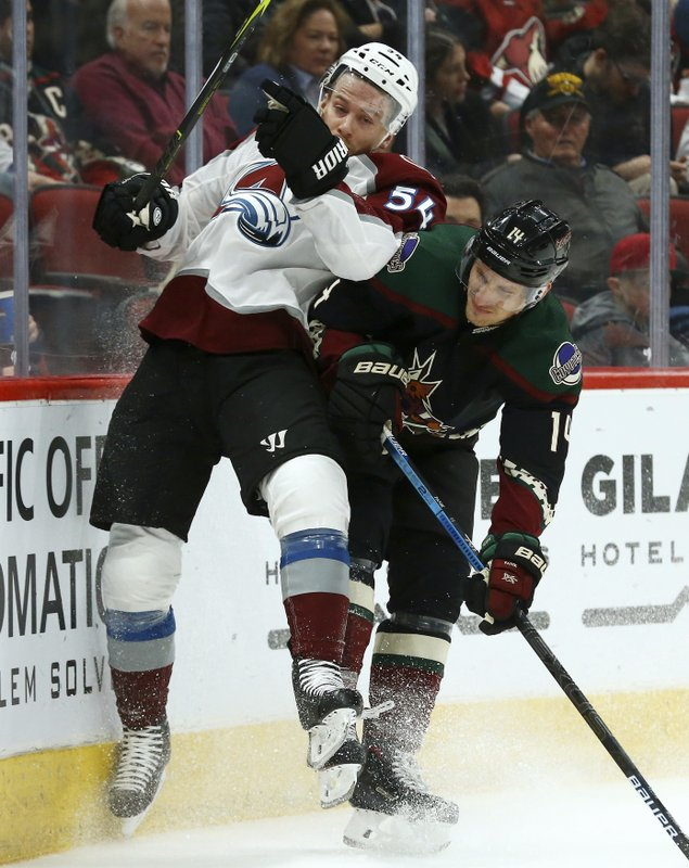 Arizona Coyotes right wing Richard Panik (14) checks Colorado Avalanche defenseman Anton Lindholm (54) into the boards during the second period of an NHL hockey game Saturday, Dec. (AP Photo/Ross D. Franklin)