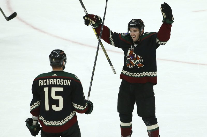 Arizona Coyotes center Brad Richardson (15) celebrates his goal against the Colorado Avalanche with Coyotes right wing Josh Archibald (45) during the third period of an NHL hockey game Saturday, Dec. (AP Photo/Ross D. Franklin)
