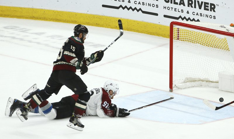 Arizona Coyotes center Brad Richardson (15) scores an empty net goal as Colorado Avalanche left wing Gabriel Landeskog (92) is unable to stop the puck during the third period of an NHL hockey game Saturday, Dec. (AP Photo/Ross D. Franklin)