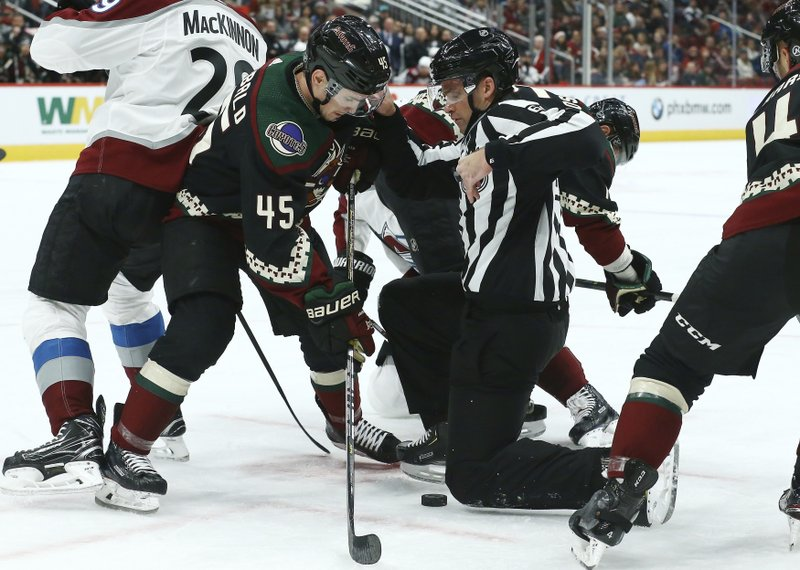 Arizona Coyotes right wing Josh Archibald (45) tries to get to the puck as linesman Brandon Gawryletz moves out of the way during the first period of an NHL hockey game against the Colorado Avalanche Saturday, Dec. (AP Photo/Ross D. Franklin)