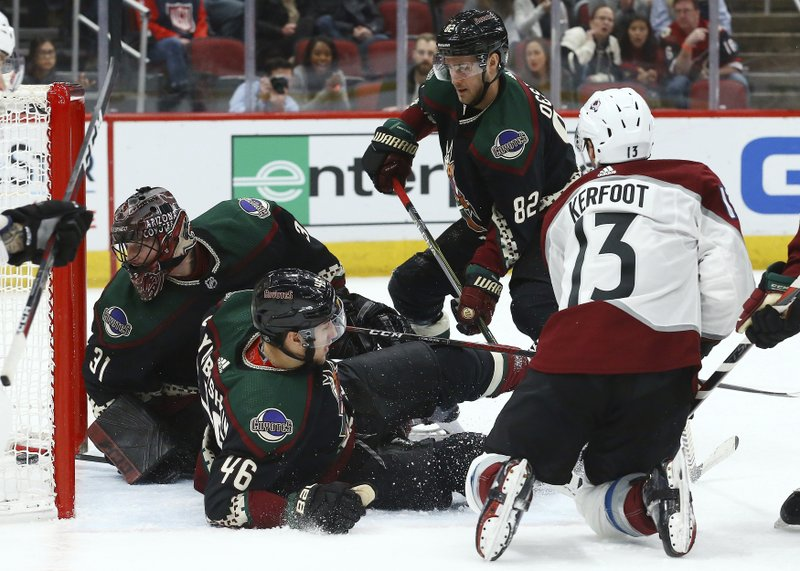 Colorado Avalanche center Alexander Kerfoot (13) gets the puck past Arizona Coyotes defenseman Ilya Lyubushkin (46), defenseman Jordan Oesterle (82) and goaltender Adin Hill (31) for a goal during the first period of an NHL hockey game Saturday, Dec. (AP Photo/Ross D. Franklin)