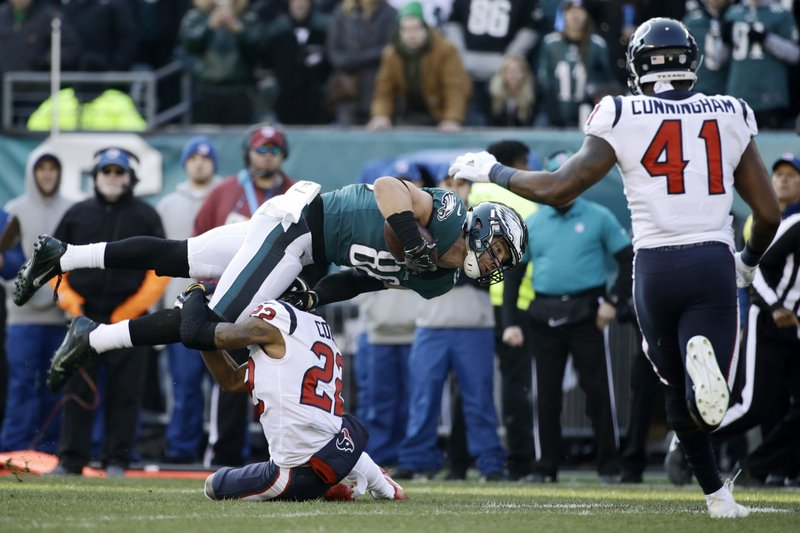 Philadelphia Eagles' Zach Ertz (86) is tackled by Houston Texans' Aaron Colvin (22) as Zach Cunningham (41) runs in during the first half of an NFL football game, Sunday, Dec. (AP Photo/Matt Rourke)