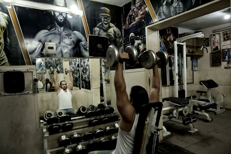 In this Oct. 23, 2018 photo, a man lifts barbells at a gym in the Shubra neighborhood of Cairo, Egypt. (AP Photo/Nariman El-Mofty)