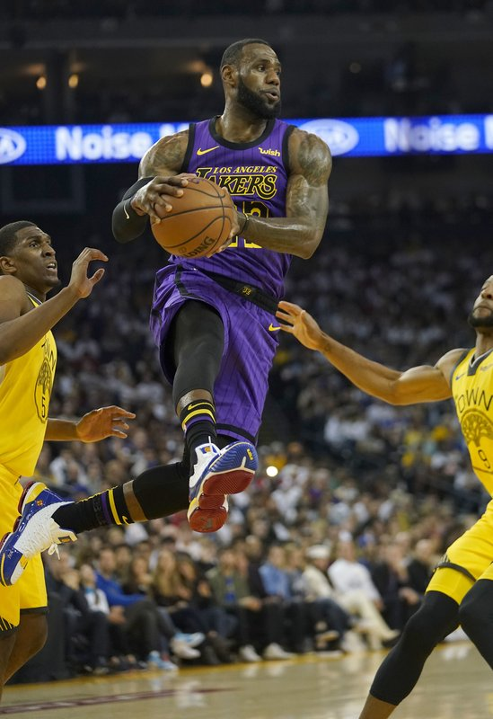 Los Angeles Lakers forward LeBron James (23) drives between Golden State Warriors' Kevon Looney (5) and Andre Iguodala during the first half of an NBA basketball game Tuesday, Dec. (AP Photo/Tony Avelar)