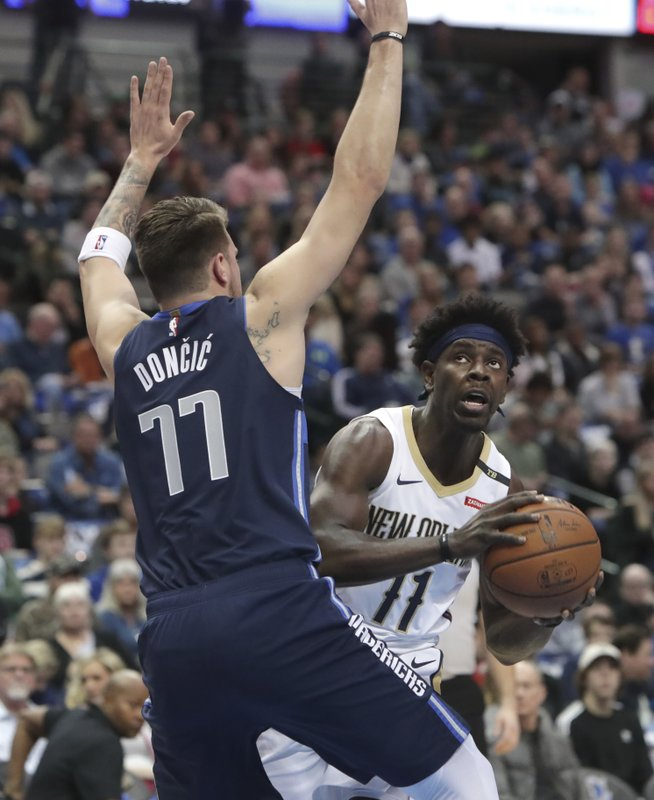 New Orleans Pelicans guard Jrue Holiday (11) looks to shoot against Dallas Mavericks forward Luka Doncic (77) during the first half of an NBA basketball game in Dallas, Wednesday, Dec. (AP Photo/LM Otero)