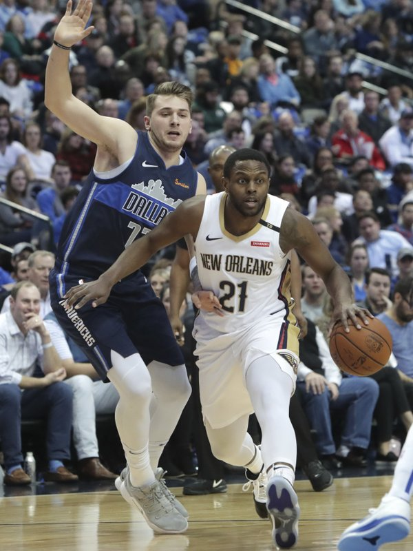 New Orleans Pelicans forward Darius Miller (21) drives past Dallas Mavericks forward Luka Doncic (77) during the first half of an NBA basketball game in Dallas, Wednesday, Dec. (AP Photo/LM Otero)