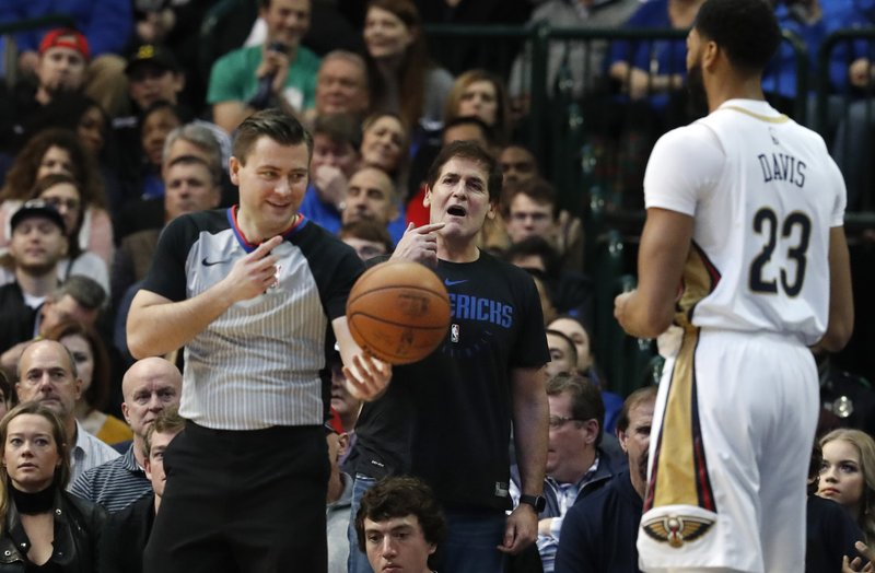 Dallas Mavericks owner Mark Cuban, center, has words for referee Gediminas Petraitis, left, as New Orleans Pelicans forward Anthony Davis (23) looks on during the first half of an NBA basketball game in Dallas, Wednesday, Dec. (AP Photo/LM Otero)