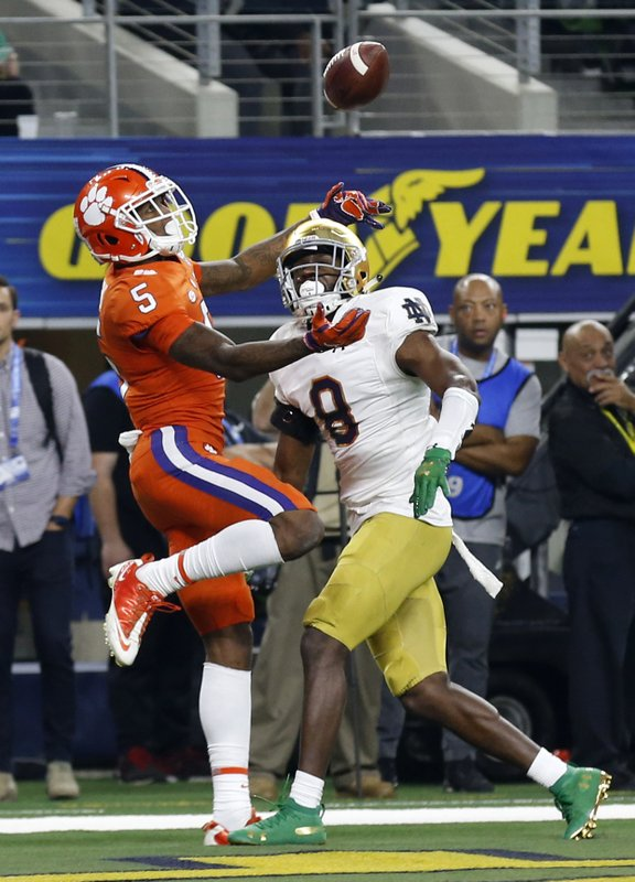 Clemson wide receiver Tee Higgins (5) reaches up to catch a ball that was tipped by Notre Dame cornerback Donte Vaughn (8) in the end zone for a touchdown late in the first half of the NCAA Cotton Bowl semi-final playoff football game, Saturday, Dec. (AP Photo/Roger Steinman)