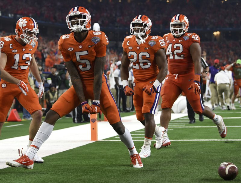 Clemson wide receiver Tee Higgins (5) celebrates his touchdown catch with wide receiver Hunter Renfrow (13), running back Adam Choice (26) and linebacker John Boyd (46) in the first half of the NCAA Cotton Bowl semi-final playoff football game against Notre Dame on Saturday, Dec. (AP Photo/Jeffrey McWhorter)