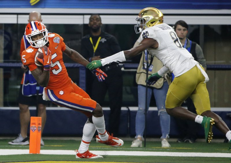 Clemson wide receiver Tee Higgins (5) comes down with control of the ball that was tipped by Notre Dame cornerback Donte Vaughn (8) in the end zone for a touchdown late in the first half of the NCAA Cotton Bowl semi-final playoff football game, Saturday, Dec. (AP Photo/Michael Ainsworth)
