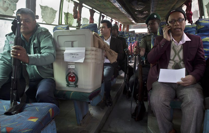 Bangladeshi polling officials accompanied by police personnel wait inside a bus before leaving for a polling station on the eve of the general elections in Dhaka, Bangladesh, Saturday, Dec. (AP Photo/Anupam Nath)