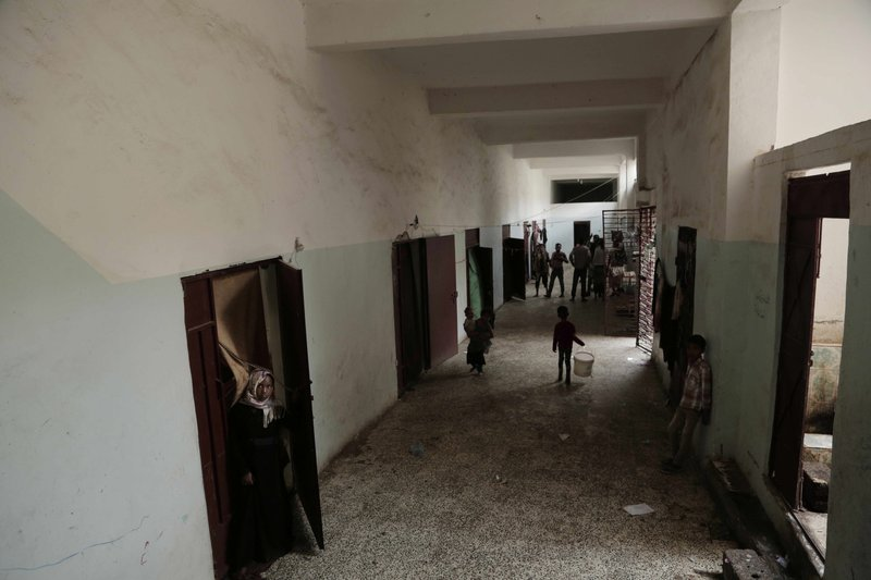 People stand near their rooms inside a shelter for displaced persons in Ibb, Yemen, in this Aug. 3, 2018, photo. (AP Photo/Nariman El-Mofty)