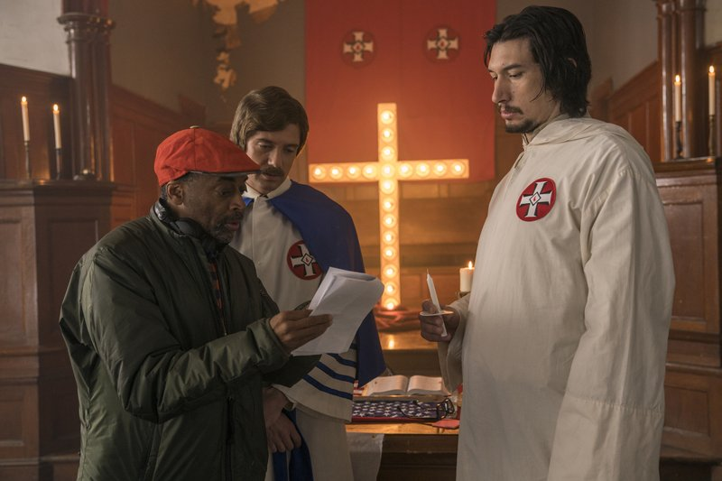 This image released by Focus Features shows director Spike Lee, left, with actors Topher Grace, center, and Adam Driver on the set of Lee's film