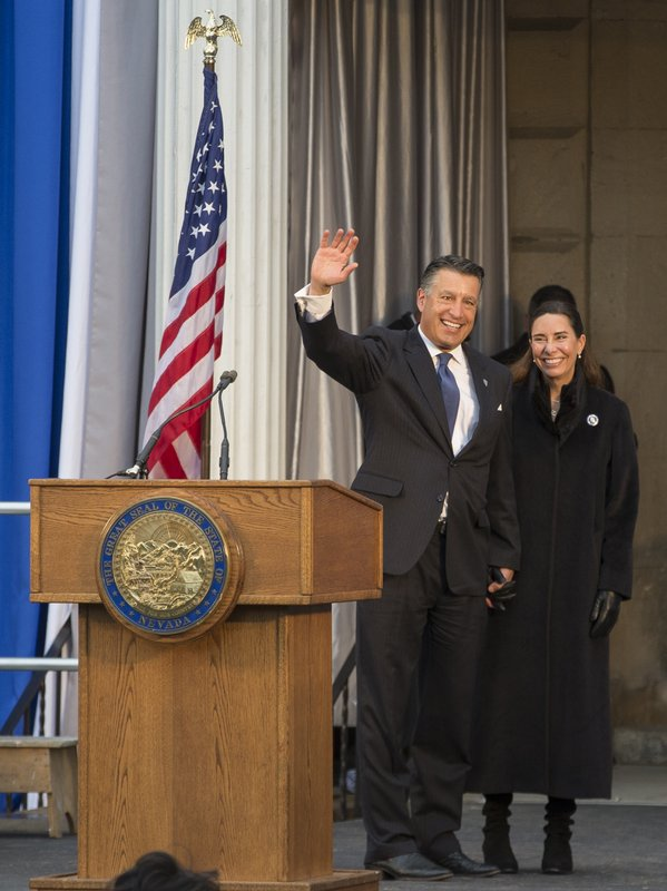 Governor Brian Sandoval, with wife Lauralyn McCarthy, gives one last wave as governor before Governor-elect Steve Sisolak is sworn into office on the steps of the Nevada State Capitol in Carson City, Nev. (AP Photo/Tom R. Smedes)