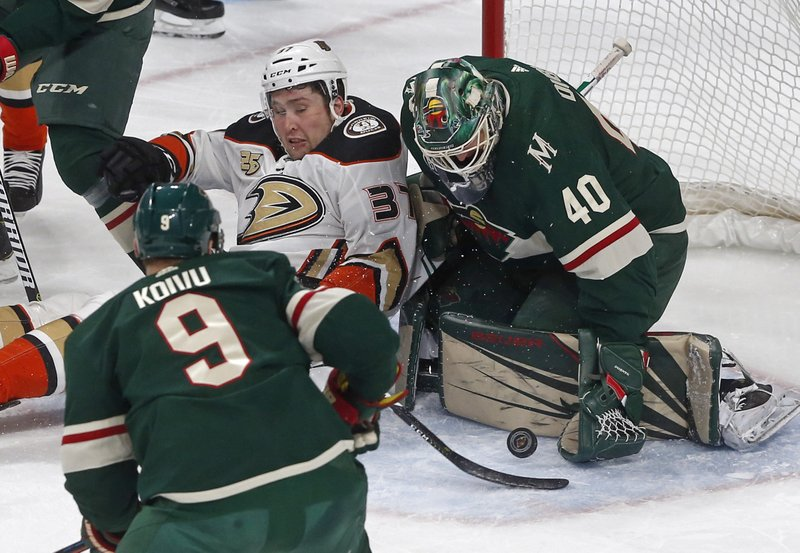 Anaheim Ducks' Nick Ritchie (37) lands on the ice as Minnesota Wild goalie Devan Dubnyk stops a shot in the first period of an NHL hockey game, Thursday, Jan. (AP Photo/Jim Mone)