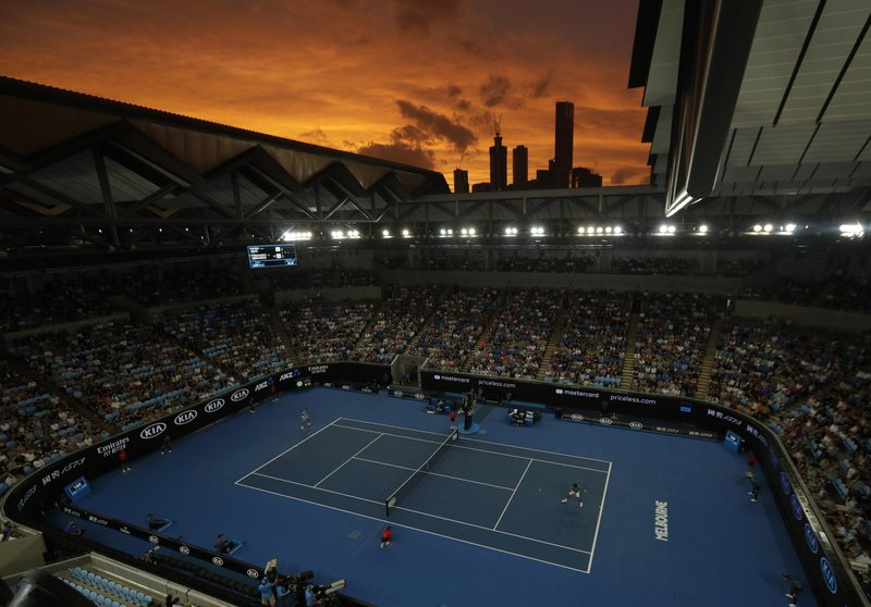 The sun sets over the Melbourne skyline as Croatia's Marin Cilic and Spain's Fernando Verdasco play their third round match at the Australian Open tennis championships in Melbourne, Australia, Friday, Jan. (AP Photo/Mark Schiefelbein)