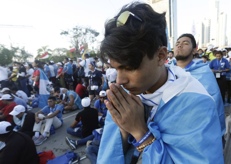 A pilgrim prays during a Stations of the Cross event lead by Pope Francis at Campo Santa Maria la Antigua, along the Cinta Costera of Panama City, Friday, Jan. (AP Photo/Arnulfo Franco)