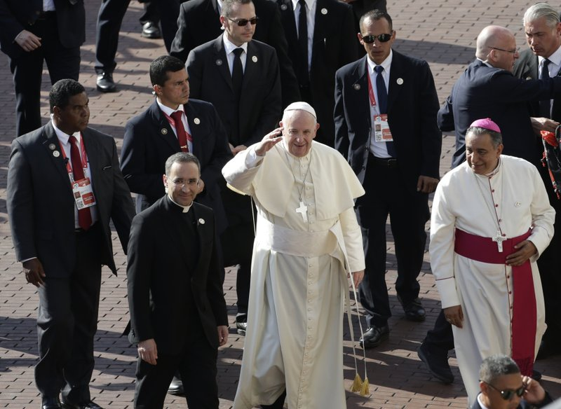 Flanked by a security detail, Father Mauricio Rueda Beltz, papal trip organizer, left, and Panama Archbishop Jose Domingo Ulloa, Pope Francis waves as he arrive to a celebrate Mass in the Santa Maria La Antigua cathedral in Panama City, Saturday, Jan. (AP Photo/Arnulfo Franco)