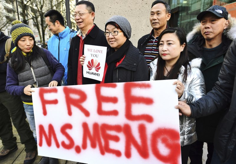 FILE - In this Dec. 10, 2010, file photo, supporters hold a sign of support for Meng Wanzhou, Huawei's chief financial officer prior to her bail hearing at a Vancouver, British Columbia courthouse. (Jonathan Hayward/The Canadian Press via AP, File)