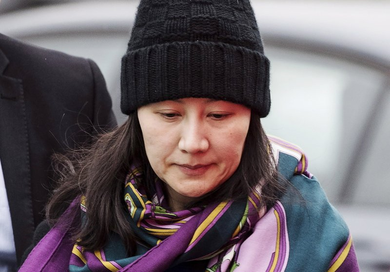 FILE - In this Dec. 12, 2018, file photo, Huawei chief financial officer Meng Wanzhou arrives at a parole office with a security guard in Vancouver, British Columbia. (Darryl Dyck/The Canadian Press via AP, File)