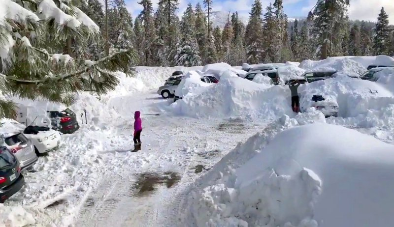 This Wednesday,, Feb. 6, 2019 photo from video by Joel Keeler shows people attempting to clear cars buried in the parking lot of the showed-in Montecito Sequoia Lodge in Kings Canyon National Park in California's Sierra Nevada. (Joel Keeler via AP)