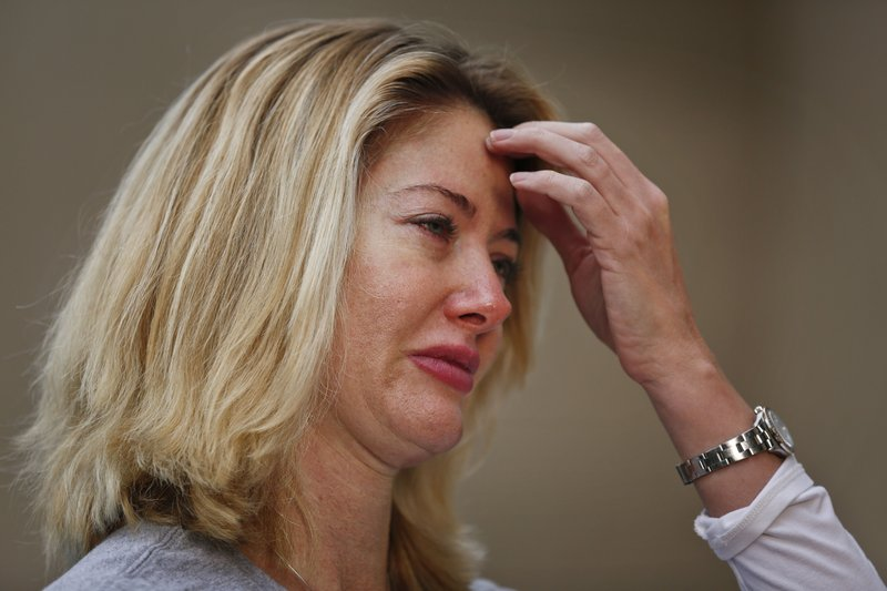 In this Jan. 30, 2019, photo, Mechelle Boyle, who appeared in an iconic image comforting Cathi Rush during the Marjory Stoneman Douglas High School shooting, cries as she speaks during an Associated Press interview about the anniversary of the shooting in Parkland, Fla. (AP Photo/Brynn Anderson)