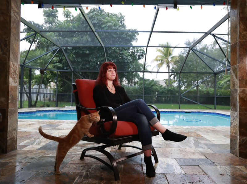 In this Jan. 28, 2019 photo, Cathi Rush, who appeared in an iconic image with Mechelle Boyle after the Marjory Stoneman Douglas High School shooting, speaks as one of her cats comes up to watch during an interview with The Associated Press at her home in Coral Springs, Fla. (AP Photo/Wilfredo Lee)