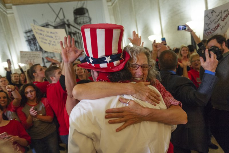 Mary Jane Helgren, an art teacher in Pleasants County, hugs Parry Caster of Huntington Explorer Academy as teachers and school personnel celebrate after the House of Delegates passed a motion to postpone indefinitely a vote on Senate Bill 451 at the West Virginia State Capitol in Charleston, W. (Craig Hudson/Charleston Gazette-Mail via AP)