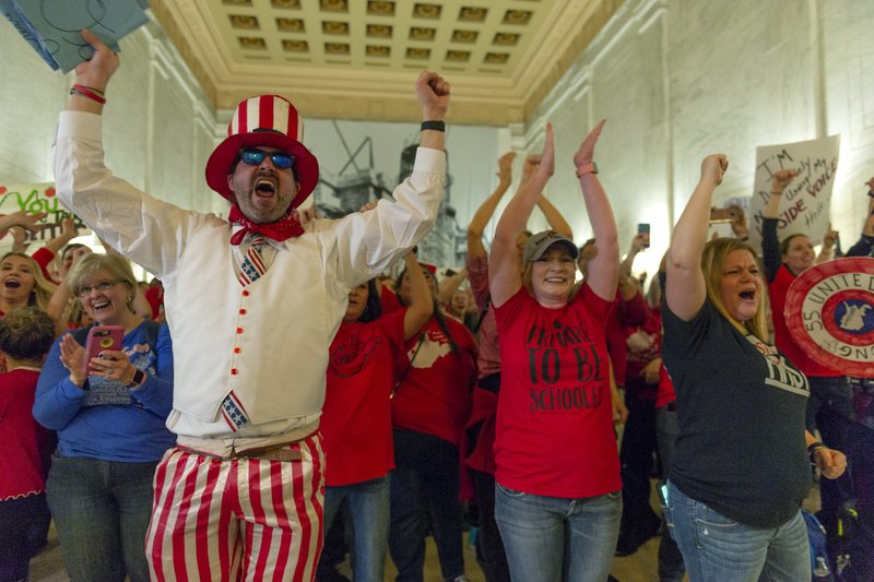 Teachers and school personnel celebrate after the House of Delegates passed a motion to postpone a vote on Senate Bill 451 indefinitely at the West Virginia State Capitol in Charleston, W. (Craig Hudson/Charleston Gazette-Mail via AP)