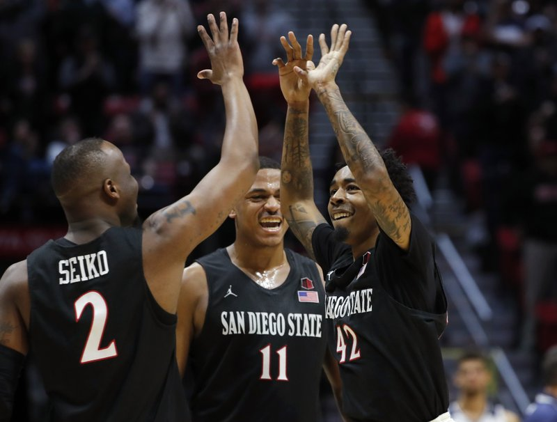 San Diego State guard Jeremy Hemsley, right, celebrates with forward Matt Mitchell (11), and guard Adam Seiko (2) during the first half of the team's NCAA college basketball game against Nevada, Wednesday, Feb. (AP Photo/Gregory Bull)