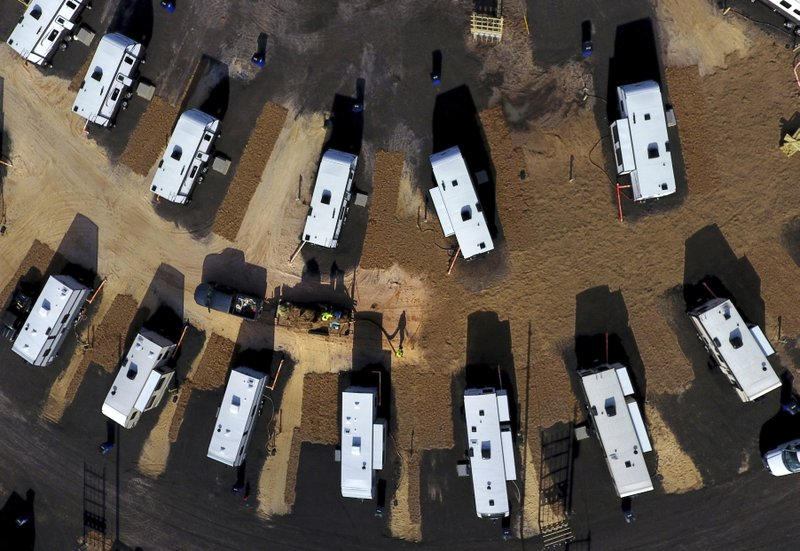 A worker sprays straw around newly setup Federal Emergency Management Agency trailers for residents left homeless by Hurricane Michael in Panama City, Fla, Thursday, Jan. (AP Photo/David Goldman)