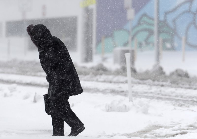 A lone pedestrian struggles along Broadway as a late winter storm packing hurricane-force winds and snow sweeps over the intermountain West Wednesday, March 13, 2019, in Denver. (AP Photo/David Zalubowski)