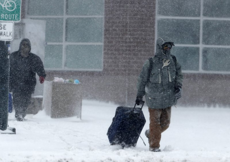 A traveller drags a suitcase as a late winter storm packing hurricane-force winds and snow sweeps over the intermountain West Wednesday, March 13, 2019, in Denver. (AP Photo/David Zalubowski)