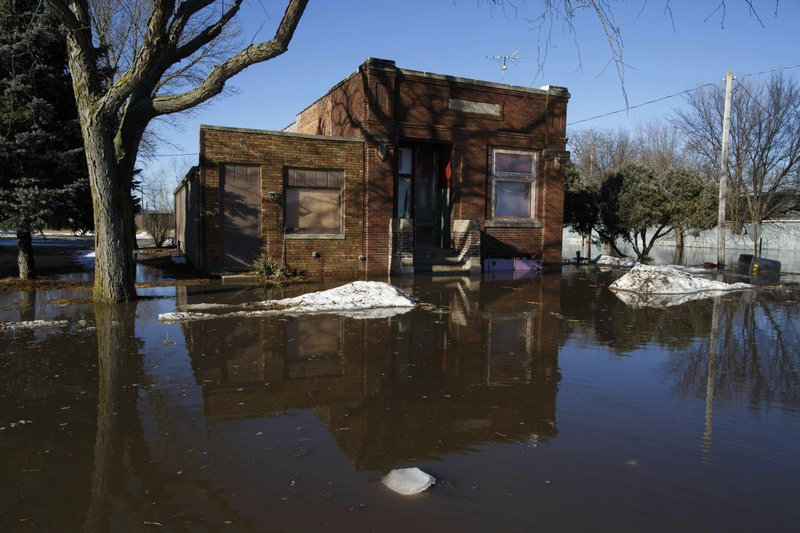 High water floods a street Wednesday, March 13, 2019, in Hooper, Neb. A window-rattling late winter storm brought blizzards, floods and a tornado across more than 25 states Wednesday, stretching from the northern Rocky Mountains to Texas and beyond. (Ryan Soderlin/Omaha World-Herald via AP)