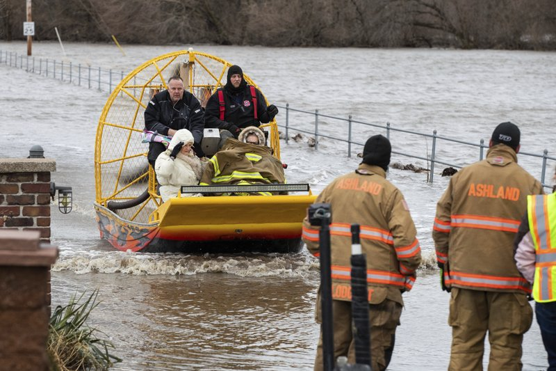 Mary Roncka and her husband Gene Roncka, right, accompanied by neighbor Kevin Mandina are evacuated as floodwaters rise Thursday, March 13, 2019, in Ashland, Neb. (Brendan Sullivan/Omaha World-Herald via AP)
