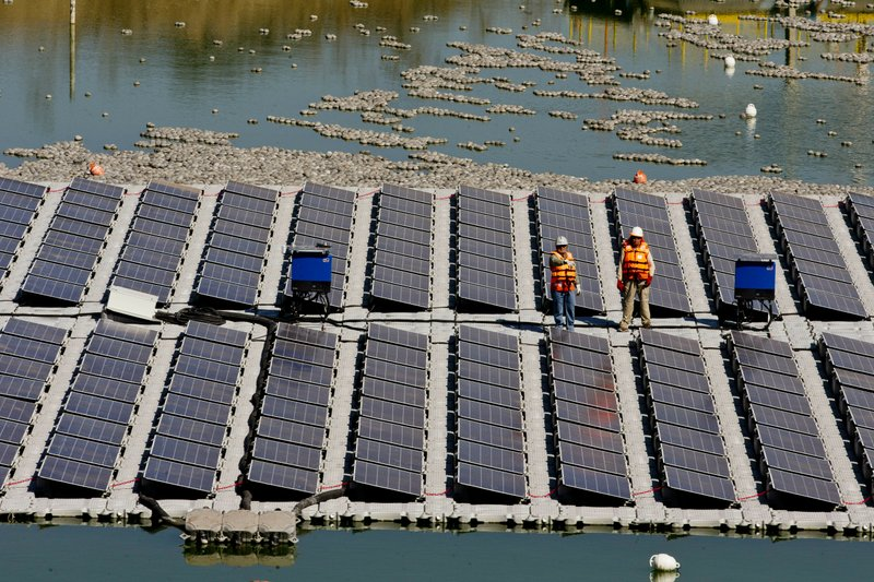 Workers stand on a floating island of solar panels on a pond at Los Bronces mine, about 65 kilometers (approximately 40 miles) from Santiago, Chile, Thursday, March 14, 2019. (AP Photo/Esteban Felix)