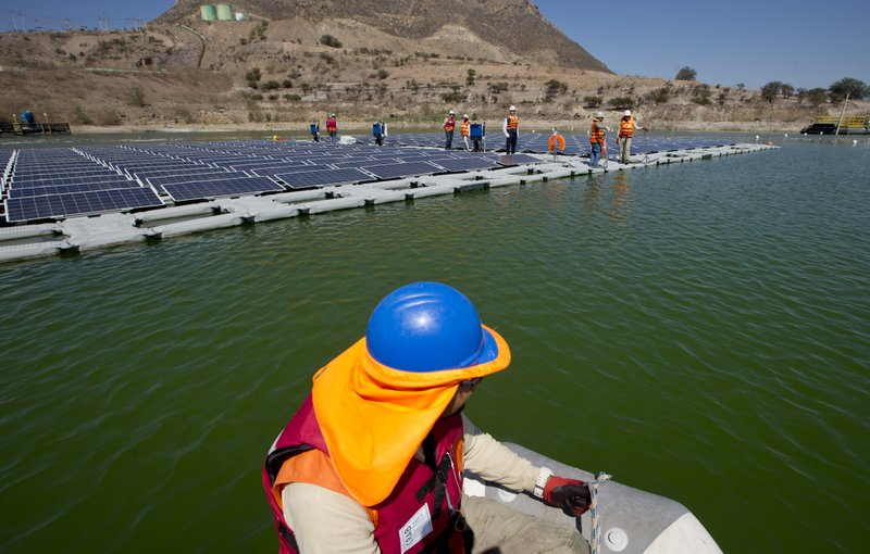 A worker on a boat approaches a floating island of solar panels at Los Bronces mine, about 65 kilometers (approximately 40 miles) from Santiago, Chile, Thursday, March 14, 2019. (11,500 feet) above sea level. In 2018, the mine produced 370,000 tons of fine copper and 2,421 tons of molybdenum. (AP Photo / Esteban Felix)