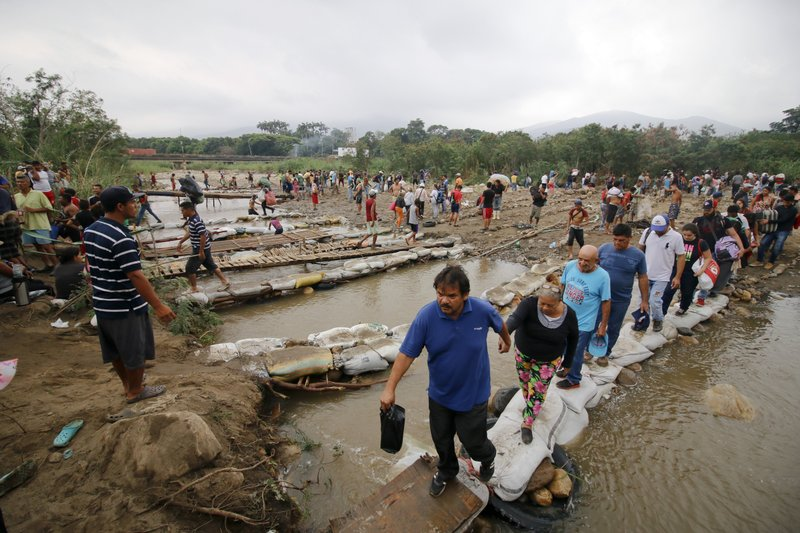 People cross the Tachira River into Colombia near the Simon Bolivar International bridge, which Venezuelan authorities only open to students and the sick, in Cucuta, Colombia, Tuesday, March 12, 2019, on the border with Venezuela. (AP Photo/Schneyder Mendoza)