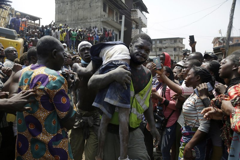 A body of a child is recovered from the rubble of a collapsed building in Lagos, Nigeria, Wednesday March 13, 2019. (AP Photo/Sunday Alamba)