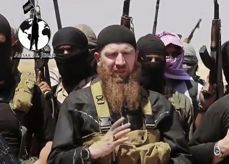 FILE - This file image made from undated video posted during the weekend of June 28, 2014, on a social media account frequently used for communications by the Islamic State of Iraq and the Levant (ISIL), which has been verified and is consistent with other AP reporting, shows Omar al-Shishani standing next to the group's spokesman among a group of fighters as they declare the elimination of the border between Iraq and Syria. (AP Photo/militant social media account via AP video, File)