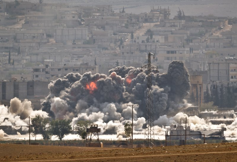 FILE - In this October 28, 2014, file photo, smoke and flames rise from an Islamic State fighters' position in the town of Kobani during airstrikes by the US-led coalition seen from the outskirts of Suruc, near the Turkey-Syria border. (AP Photo/Vadim Ghirda, File)