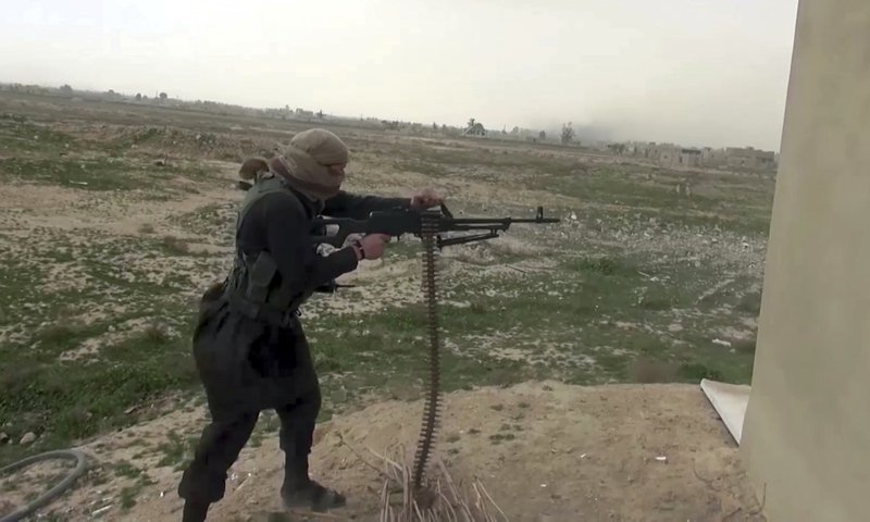 FILE - This a file frame grab from video posted online Friday, Jan. 18, 2019, by supporters of the Islamic State group, purports to show an IS fighter firing a weapon during clashes with members of the U. (Militant Photo via AP, File)