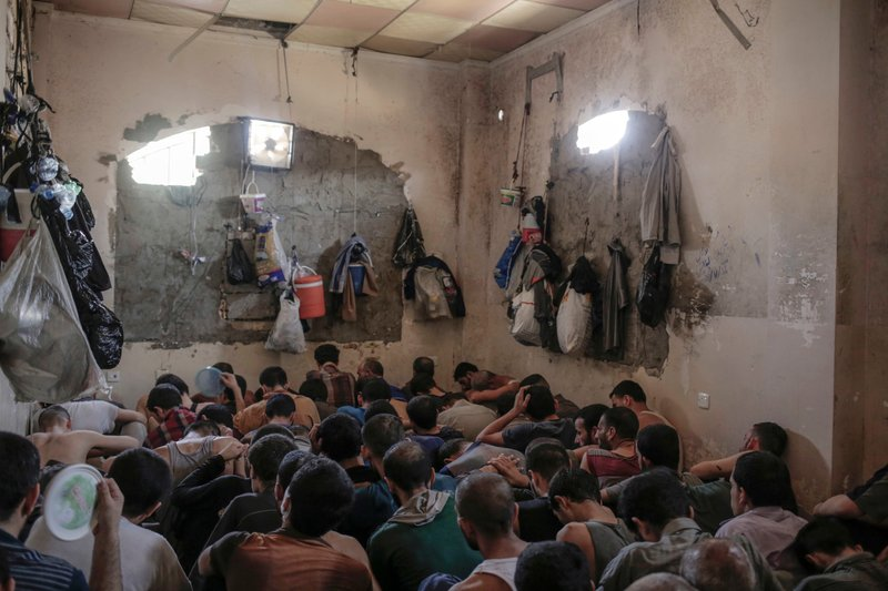 FILE -In this Tuesday, July 18, 2017, file photo, suspected Islamic State members sit inside a small room in a prison south of Mosul. (AP Photo/Bram Janssen, File)