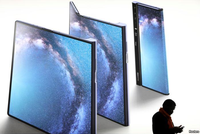 A man checks his phone next to an advertisement of a new Huawei Mate X device