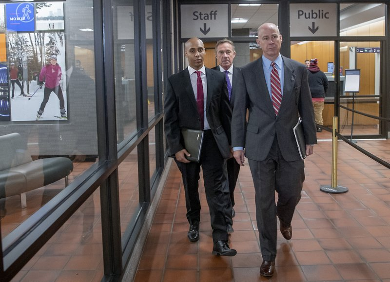 Former Minneapolis police officer Mohamed Noor, left, and his attorneys Peter Wold, center, and Thomas Plunkett, right, made their way out of court at the Hennepin County Government Center, Monday, April 1, 2019 in Minneapolis, Minn. (Elizabeth Flores/Star Tribune via AP)