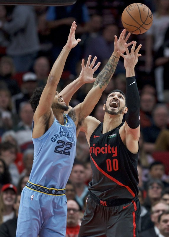 Portland Trail Blazers center Enes Kanter, right, and Memphis Grizzlies guard Tyler Dorsey vie for a rebound during the first half of an NBA basketball game in Portland, Ore. (AP Photo/Craig Mitchelldyer)